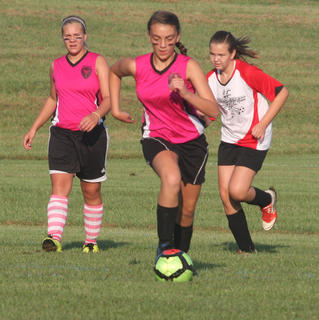 Paige Fulkerson of the U12 Nelson County Shockwave works the ball upfield in a game at the Bluegrass State Games over the weekend. Teammate Paige Dones (left) backs up the play.