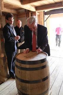 Kentucky Governor Steve Beshear signs the first barrel of bourbon to be stored in Heaven Hill's new rickhouse.