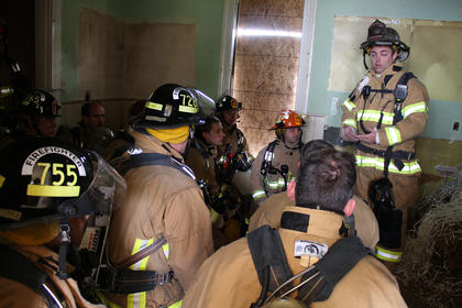 State Fire Instructor Todd Vinton prepares firefighters for what they're about to experience. A pile of wood and shredded paper, seen at right, will soon be set ablaze, and kneeling firefighters in face masks will watch the flames crawl across the ceiling above their heads.