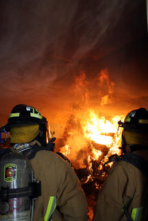 """Firefighters David Neel and Scott Mattingly look on as a layer of smoke streams above their head and out the door behind them. Smoke forms a """"thermal layer"""" that lowers as it fills up a room."""