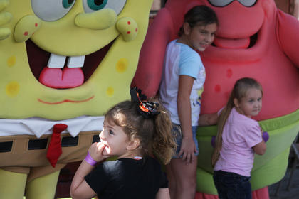 Ashlyn Edge, 3, Ohio County, meets SpongeBob SquarePants while sisters Destiny Shaw, 10, and Emily Metcalf, 4, both of Hodgenville, take a picture with Patrick the starfish during the television stars' visit to the Kentucky Railway Museum in New Haven Sunday.