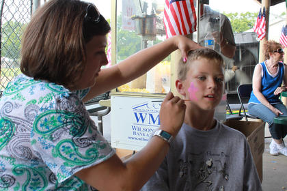 Tina Long of the Northeast Nelson Community Development Association paints the face of Nolan Key, 10, Bardstown, at the Bloomfield Picnic in the Park July 9, 2011.