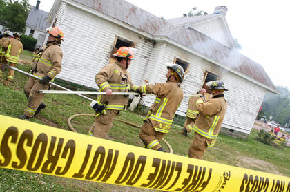 Firefighters prepare to set the house ablaze after a day of training.