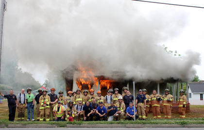 Members of the Bardstown-Nelson County Fire Department and state fire instructors pose as a house fire rages behind them after a day of training.