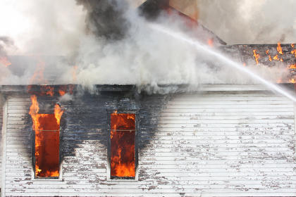 Flames flickered from the windows of the house at 715 N. Third St. as firefighters cool the blaze with a stream of water. The house was allowed to burn after the day was spent lighting and extinguishing smaller fires for training.