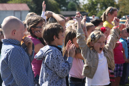 """Hannah Keeling cheers as a school bus moves out from in front of the entrance to Foster Heights Elementary School's new gymnasium and media center Monday. Students chanted """"move that bus"""" (à la the television show """"Extreme Home Makeover"""") as the entrance was revealed. Also pictured are Cameron Crepps, center, and Adam Fulkerson. All three are students in Sara Beth Mattingly's second-grade class."""