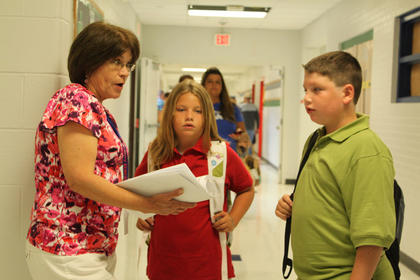 Fifth-grader Dalton Mills and fourth-grader Ashley Mills ask art teacher Micki Yonts how to find their classrooms on the first day of the 2011-2012 school year Aug. 3.