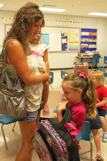Carli Hart, 5, doesn't want to put her backpack in her cubby on a nervous first day of kindergarten in Toni Ice's class at Foster Heights Elementary School Aug. 3. Her mother, Rhondalyn Hart, and sister, Addison Hart, 3, encourage her.