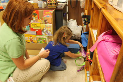 Teacher Toni Ice helps Caroline Wade, 5, find her cubby during her first day of kindergarten at Foster Heights Elementary Wednesday.