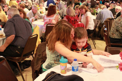 Lee Miller and her two-year-old Kaleb Miller draw a picture at the Taste of Bardstown event April 11.