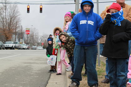 Connor Baker, right, and his brother, Chase Baker, center, were among the many kids waiting eagerly for the first floats of the New Haven Christmas Parade to come driving by.