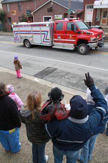 Paul DeWitt, his great nephew Ben Hansen in one arm, waves to a Rolling Fork Volunteer Fire Department emergency vehicle. Firetrucks led the convey of floats during Sunday's parade.