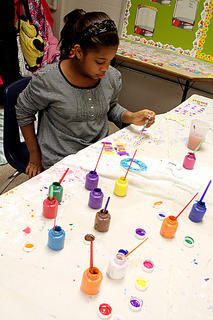 "Bardstown Elementary School fifth-grader Tohri Dodson paints the letters of her name as part of the Bardstown City Schools enrichment class, ""It's a Daytime Slumber Party,"" Thursday morning. Students got to come to school in their pajamas and do all sorts of arts and crafts, from making chalkboards out of pizza pans to painting pillowcases."