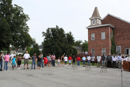 About 50 volunteers pray together before kicking off the renovation of the 199-year-old First Baptist Church Aug. 13 in preparation for its conversion into the Reverend Roy Henry Educational Center. According to co-organizer Lucretia Young, the group removed about three dumpsters full of items between 9 a.m. and 4:30 p.m.
