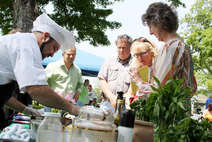 "Chef and master gardener Jon Askelson, who founded Local Fare Farms in Balltown with his wife, Shannon, recently, serves samples of herb-based foods at the second Annual Shades of Nature Herb Festival at Wickland April 28. ""Our goal is to try to get products that are locally made,"" said Askelson, who seeks to minimize his carbon footprint through his urban micro-farm. The festival featured medicinal wild plant, honey, homemade soaps and crafts and a cooking demonstration by Askelson. Also pictured are, from right, event organizer Mary Ray, and David and Bernie Sutherland of Bardstown."
