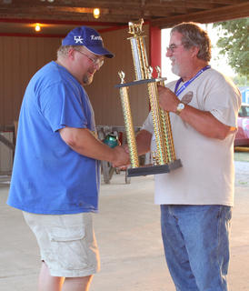 Jay Goodman, Glendale, took first place in the beef division at the Bourbon City BBQ Festival Cook-off Sept. 3 for his ribs in homemade sauce. Festival Director Rick Berry hands over the trophy.