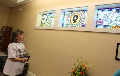 Geralyn Ellis, New Haven, admires a stained glass window custom-made with imagery from New Haven's history. Ellis' fifth great-grandfather named New Haven.
