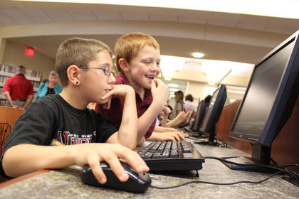 Patrick Clark, 8, left, and Cooper Penna, 7, enjoy a computer at the newly opened New Haven Branch of the Nelson County Public Library system. The grand opening was May 6.