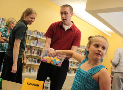 Seven-year-old Kendyl Corbin draws a door prize winner at the grand opening of the New Haven Branch of the Nelson County Public Libraries. Looking on are Technology Coordinator Emily Burkot and Assistant Director Michael Greenwell.
