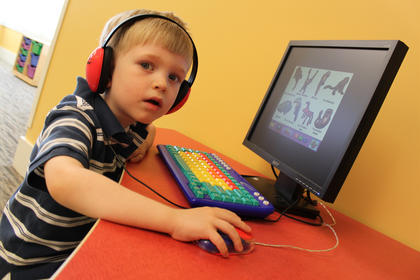 Four-year-old Logan Cox plays on the computer in the children's section of the New Haven library branch during its grand opening May 6.