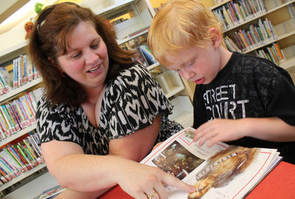 Stephanie Norman, New Haven, and 5-year-old son Caleb Norman read in the children's section of the New Haven Branch of Nelson County Public Libraries during the branch's grand opening May 6, 2012.