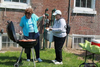 Clara Fulkerson cooked many of the hotdogs and hamburgers at the festival. Mary Jo Kruer stopped by for a hotdog.