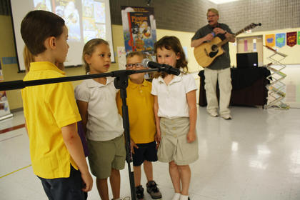 Evan Johnson, Haleigh Perry, Kaitlyn Thornton, Carson Hicks and Abbey Brown sing a song in front of their classmates as author and musician Daryl Cobb looks on during his visit to Bardstown Primary School last week.