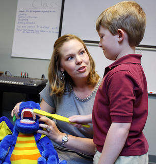 Lauren Hedgespeth instructs Landon Cissell in the proper way to brush one's teeth with the help of a stuffed animal during career day at Bluegrass Christian Academy last week.