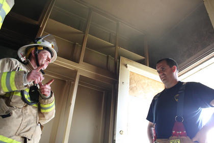 Interim Fire Chief Marlin Howard, left, speaks with State Fire Instructor Matthew Haddle inside the house as smoke hovers above their heads.