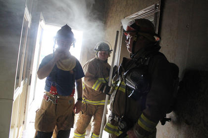 State Fire Instructor Todd Vinton, left, and firefighters check out the house during a lull in training.