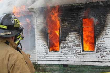 Flames flicker from the windows of the house at 715 N. Third St. as a Bardstown-Nelson County firefighter looks on May 12. It was allowed to burn after the day was spent lighting and extinguishing smaller fires for training.