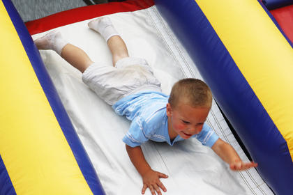 Blake O'Bryan, 2, stretches his arms out as far as he can as he slides down an inflatable at the Bourbon City Barbecue Saturday.