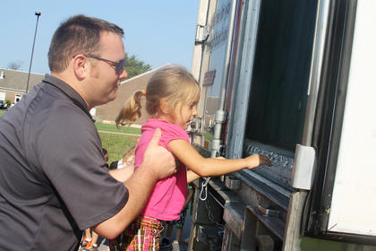 Eric Jones, a driver with Gordon Food Services, gives Tessa Grace, a kindergartener at Foster Heights Elementary, a boost to see inside his truck during career day Wednesday.