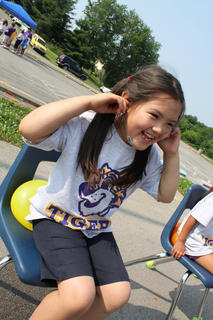 "First-grader Emi Mizutani plugs her ears in preparation for a balloon's pop at Bardstown Primary School's ""Tigerpawlooza"" field day Friday."