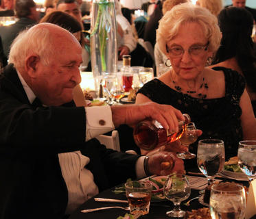 Jimmy Russell, master distiller at Wild Turkey, pours a bottle of 1792 bourbon for his wife, Joretta Russell, at the Great Kentucky Bourbon Tasting & Gala Saturday evening.