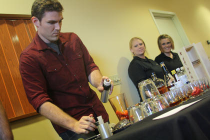Angie Leak and Heather Richards, right, representing the Old Talbott Tavern, watch as Blake Borah, left, representing the Oak Room, lights strawberries on fire for his mixed drink submission during the Kentucky Bourbon Festival Mixed Drink Challenge.  At one point, Borah's flame caused the fire alarm to sound.