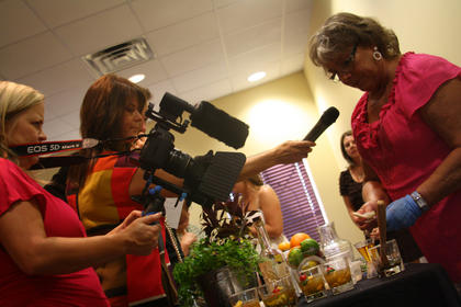"Olivia Ripy, of Lawrenceburg, right, explains how to create a mixed drink using Wild Turkey Bourbon to Kim Huston during the Kentucky Bourbon Festival Mixed Drink Challenge. Former Rand McNally representatives Nikki and Dusty Green filmed and emceed the event. Nikki and Dusty visited Bardstown in June as part of the nationwide ""Most Beautiful Small Town in America"" contest."