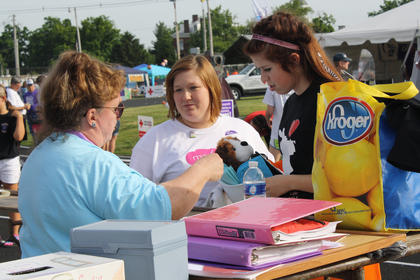 Relay Chairperson Anita Westrup, left, tells Laryn Hilderbrandt, 16, and Kelly Muncy, 30, where certain activities are located on the track.