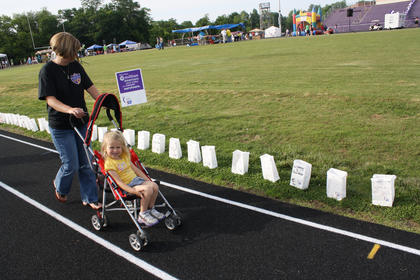 Cathy Osborne pushes her daughter, Gracie, as she observes the luminarias set around the track during Relay for Life Friday night.