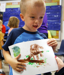 Brayden Reiter, a kindergartner, shows off a painting he made with his hands at an enrichment class at Bardstown Elementary School on Wednesday, Oct. 3.