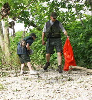 Zane Cole looks for trash amongst the plants as his father, Craig Cole, carries a bag of litter back to the canoe.