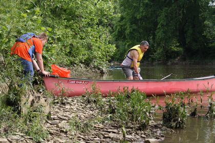 Dylan Salewski, left, helps Assistant Troop 147 Boy Scout Master Curt Elmore push a canoe after they picked up trash on the riverbank.