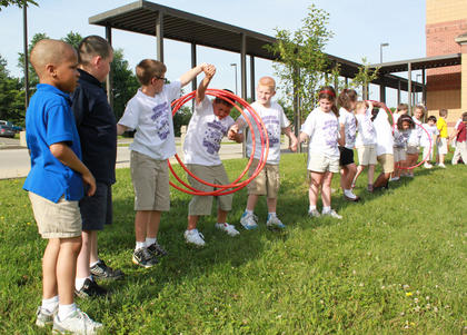 Amanda Boone and Stefani Haggard's second grade class must work together as they pass a hula hoop down a line of students at the Bardstown Primary School Tigerpawlooza field day June 2, 2011.