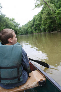 Zane Cole searches the surrounding area for trash as he travels along the river.