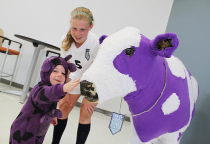 Marley Rogers, 12, encouraged her younger brother, 2-year-old Brayden Boone, to pet a life-sized stuffed purple cow, a symbol to represent how Thomas Nelson High School students stand out from the crowd, as the community toured the school June 20. Boone will be in eighth grade next year but is already a TNHS soccer player.