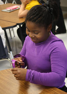 Shakira Gault, a second-grader at Bardstown Primary School, admires Reese Hoffas Olympic bronze medal.