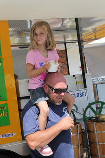 A little girl finds her father's shoulders a perfect place to watch the festival while eating an ice cream.