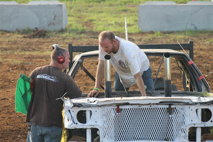 A driver climbs through the where a windshield  used to be to get a look at some damage to his car as a flagman looks on.