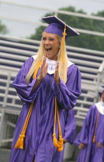 Kristin Boone claps her hands in excitment as she walks into graduation.