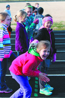 Ava Roby laughs and pretends to get a head start on the kids' one-mile race at the Bardstown school track. Watching her is her friend, Adelyn Osborne, in the jacket.